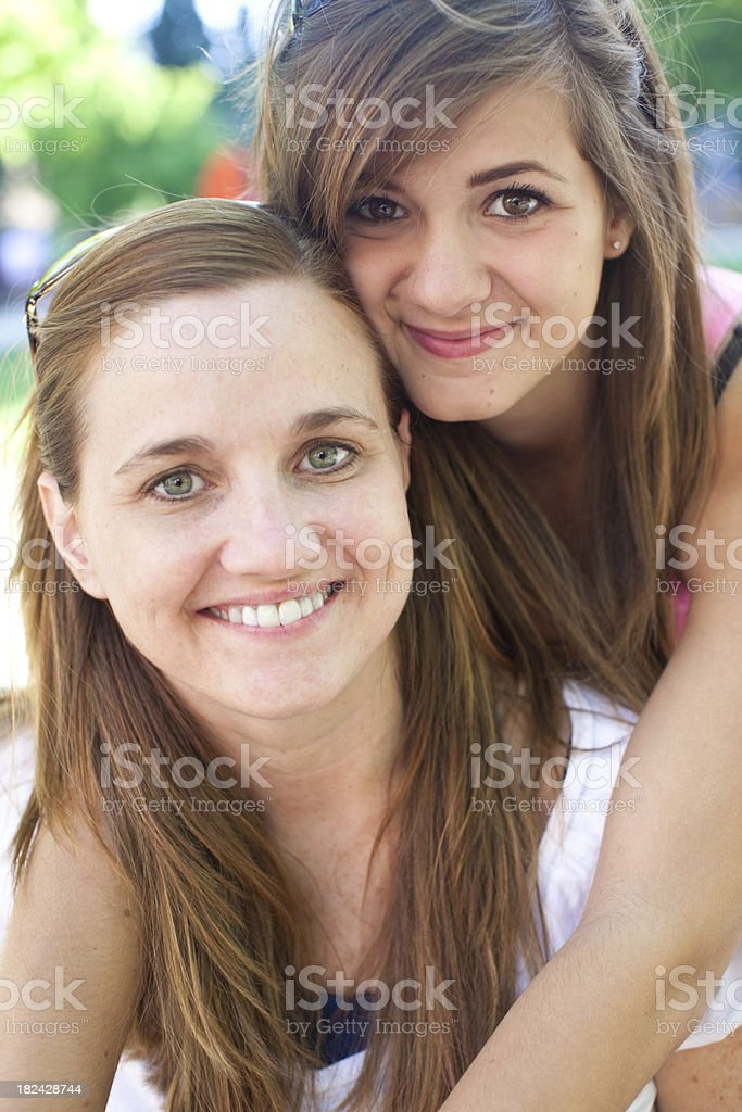 portrait of young mother with teenage daughter hugging and smiling stock photo