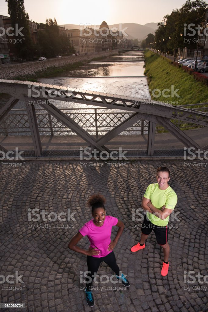 portrait of young multietnic jogging couple ready to run stock photo