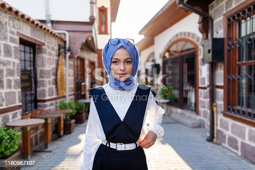 A portrait of a young and fashionable muslim woman while walking in an old town ( Hamam Onu - - ) in Ankara, Turkey.