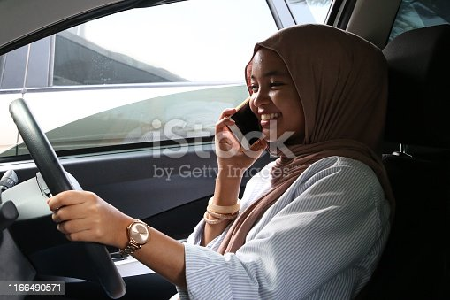 A young Muslim lady talking on smartphone cheerfully while sitting at driver's seat inside a still (not moving) car.