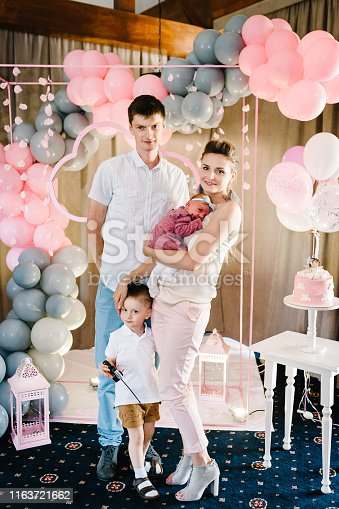 istock Portrait of young parents keep in arms, hugging child kid baby girl, celebrating birthday holiday party on pink, grey background with air balloons. Happy family: mother, father, daughter, son. 1163721662
