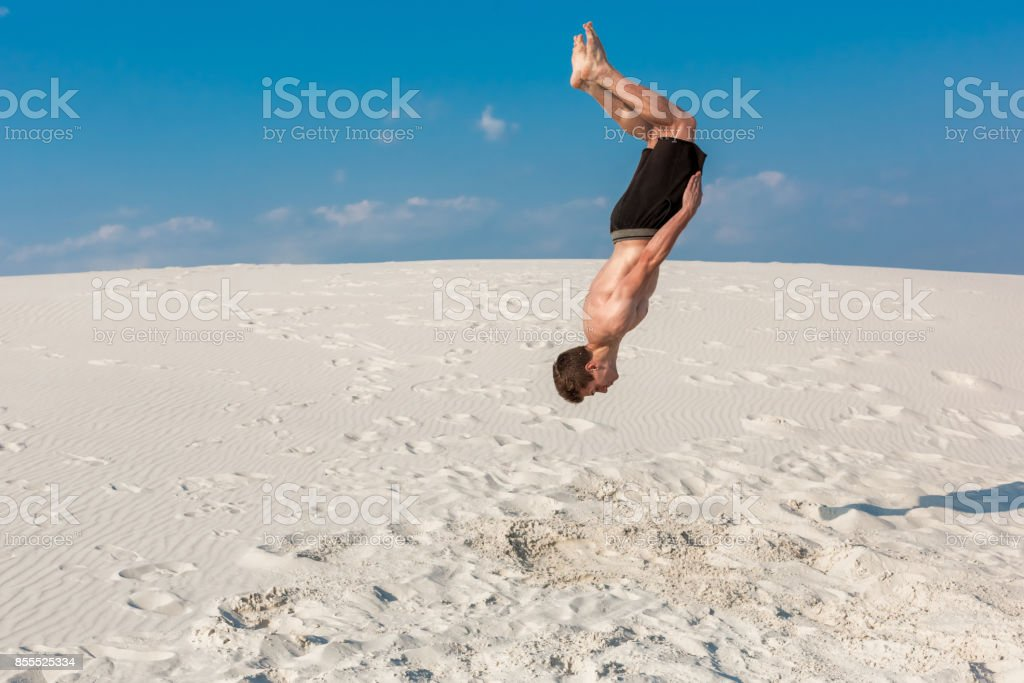 Portrait of young parkour man doing flip or somersault on the sand stock photo