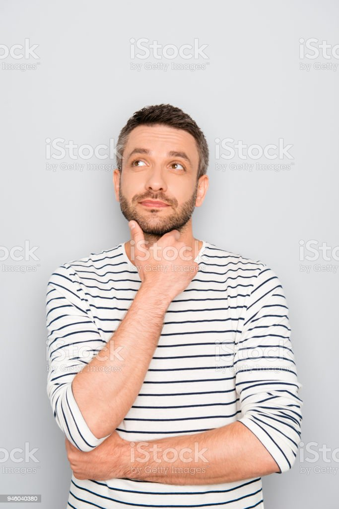 Portrait of young ponder man touching his chin stock photo