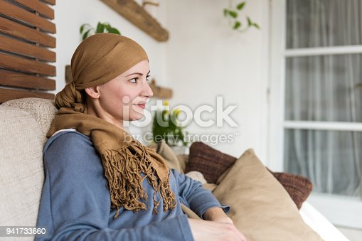 469949126 istock photo Portrait of young positive adult female cancer patient sitting in living room, smiling and watching tv. 941733660