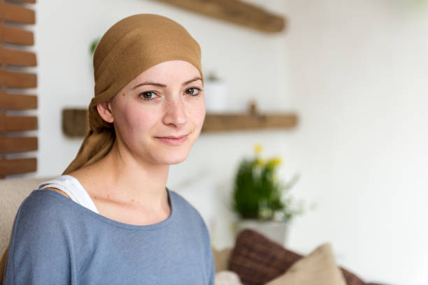 Portrait of young positive adult female cancer patient sitting in living room, smiling and looking at the camera. Portrait of young positive adult female cancer patient sitting in living room, smiling and looking at the camera. headscarf stock pictures, royalty-free photos & images