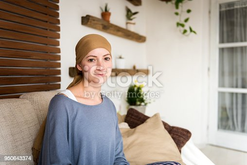 469949126 istock photo Portrait of young positive adult female cancer patient sitting in living room, smiling and looking at camera. 950643374