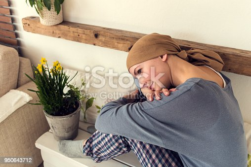 469949126 istock photo Portrait of young positive adult female cancer patient sitting in living room in her pajamas, smiling and watching tv. 950643712