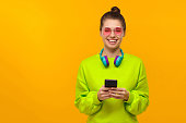 istock Portrait of young positive teenage girl wearing neon green sweatshirt, pink glasses and headphones on neck, standing with smartphone in hand, isolated on yellow background with copy space 1247694599