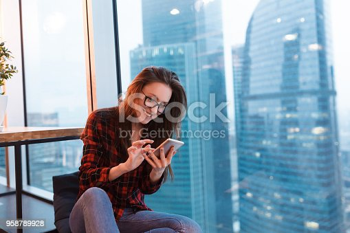 1162297213 istock photo Portrait of young positive woman in casual clothes typing text on smartphone and sitting near large office window overlooking the blurry skyscrapers 958789928