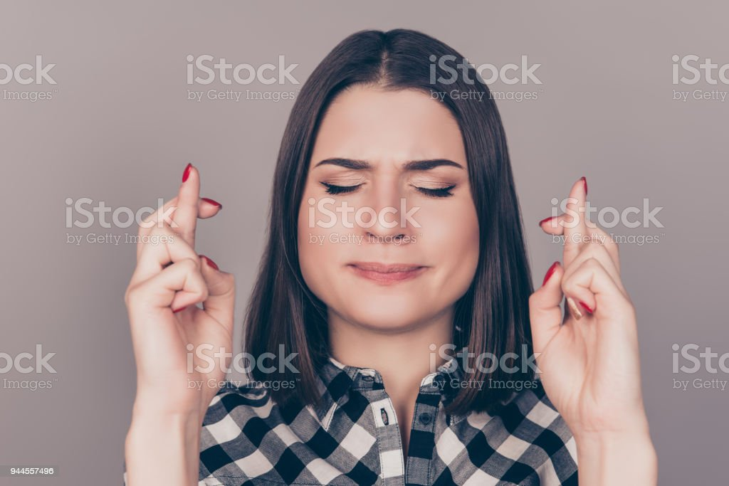 A portrait of young pretty woman with crossed fingers and closed eyes waiting for luck. Minded girl hoping for the best stock photo
