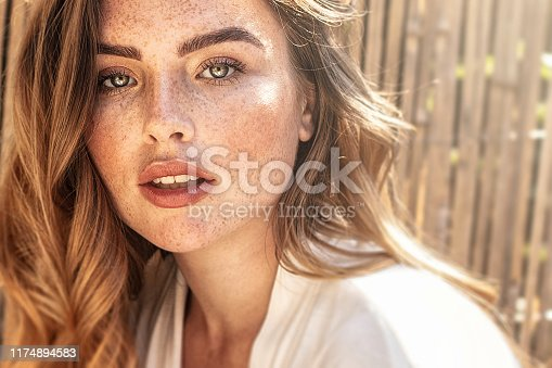Portrait of young attractive lady with long wavy red hair and freckles on her face. Woman posing on sunny summer day.