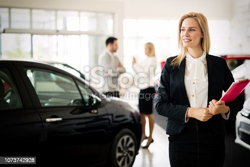 istock Portrait of young saleswoman in car dealership 1073742928