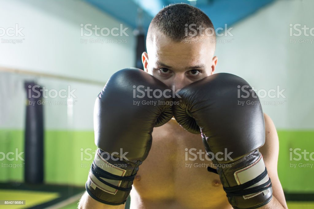 Portrait Of Young Shirtless Boxer Wearing Boxing Gloves In