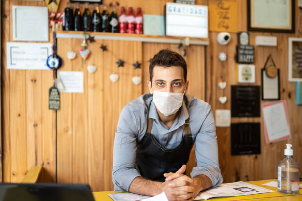 Portrait of young small business man owner with face mask at checkout stock photo