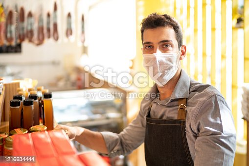 Portrait of young small business man owner with face mask working at store