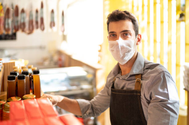 portrait of young small business man owner with face mask working at store - servizi essenziali foto e immagini stock
