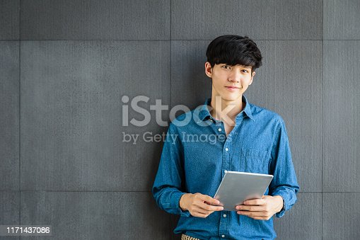 Portrait of young smiling Asian Business man holding digital tablet computer on gray background, Looking at camera