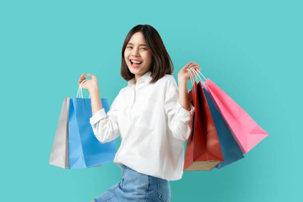 porträt der jungen lächelnden asiatischen frau lässige kleidung mit bunten einkaufstaschen auf hellblauem hintergrund. - damen jeans sale stock-fotos und bilder