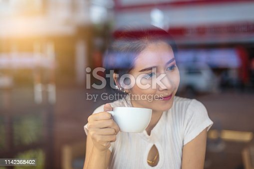 Portrait of young smiling Asian woman enjoying drinking coffee in coffee shop cafe viewed through glass with reflections