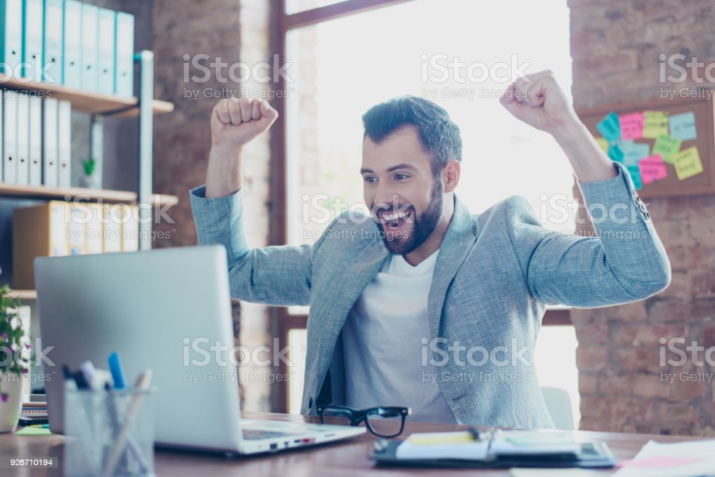 Portrait of young, smiling, attractive finansist, triumphant  having his arms with fists raised, shouting, creaming, celebrating completed work, having his mouth opened with beaming smile stock photo