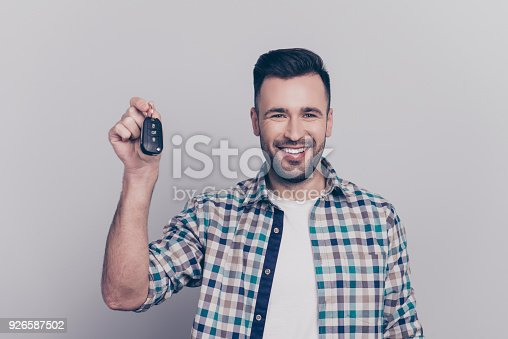 Portrait of young smiling bearded caucasian man in checkered shirt showing car key in raised hand looking at camera, lucky car owner, standing over grey background