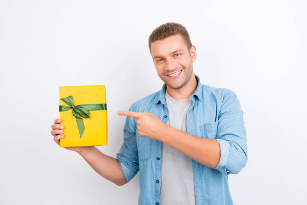 porträt von jung, lächelnd, bärtigen mann in jeans hemd demonstriert ein geschenk in einer gelben verpackung mit grünen bogen, geschenk, mit dem zeigefinger auf überragt weißem hintergrund - geburtstagsgeschenke für beste freundin stock-fotos und bilder