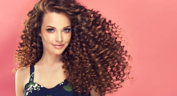 Portrait of young, smiling brown haired woman with voluminous and curly hairstyle. stock photo