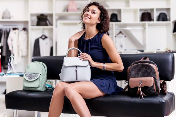 Porträt des jungen lächelnde Brünette Kommissionierung eine neue Handtasche sitzend auf einer Bank, Blick in die Kamera im Bekleidungsgeschäft. – Foto