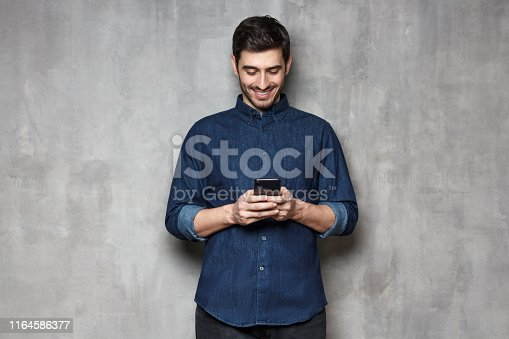 825083556istockphoto Portrait of young smiling business man typing a message with new app on his mobile phone, standing against gray textured wall 1164586377