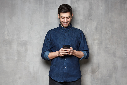 825083556 istock photo Portrait of young smiling business man typing a message with new app on his mobile phone, standing against gray textured wall 1164586377
