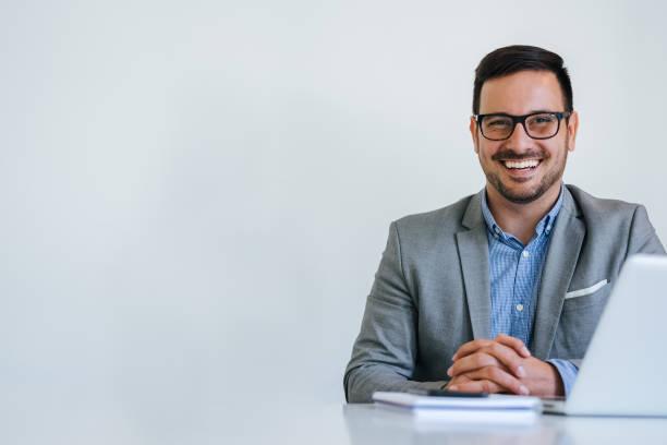 retrato do homem de negócios alegre de sorriso novo no escritório que olha o espaço da cópia da câmera - business man - fotografias e filmes do acervo