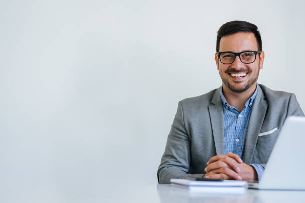 portrait of young smiling cheerful businessman in office looking at camera copy space - executivo imagens e fotografias de stock