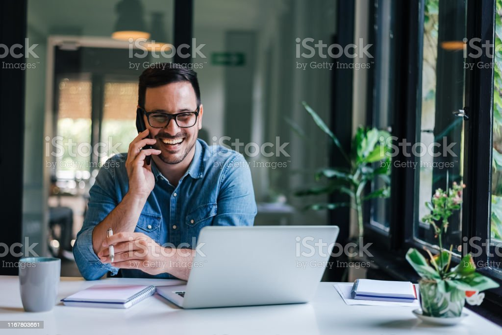 Portrait of young smiling cheerful entrepreneur in casual office making phone call while working with laptop Portrait of young smiling cheerful entrepreneur in casual office making phone call while working with laptop Adult Stock Photo