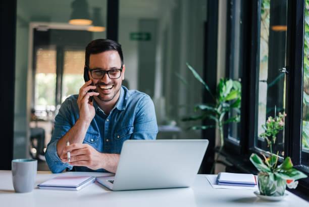 retrato de joven emprendedor alegre sonriente en la oficina casual haciendo llamadas telefónicas mientras trabaja con computadora portátil - trabajo freelance fotografías e imágenes de stock