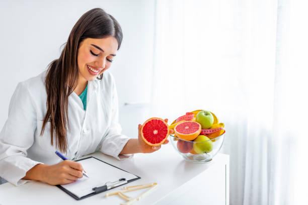 porträt einer jungen lächelnden ernährungsberaterin im sprechzimmer - ernährungsberater stock-fotos und bilder