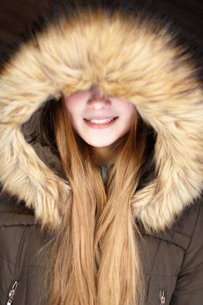 Portrait of Young smiling girl under hood Portrait of Young smiling girl with long hair under fur hood sergionicr stock pictures, royalty-free photos & images