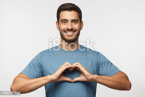 istock Portrait of young smiling man in blue t-shirt showing heart sign isolated on gray background 1041127044