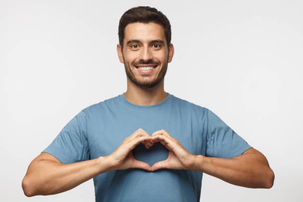 porträt der jungen lächelnd mann im blauen t-shirt zeigt herzschild auf grauem hintergrund isoliert - gestikulieren stock-fotos und bilder