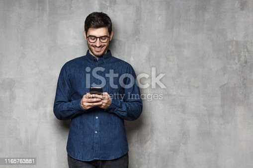 825083556istockphoto Portrait of young smiling man typing a message with new app on his smartphone, standing against gray textured wall with copy space 1165763881