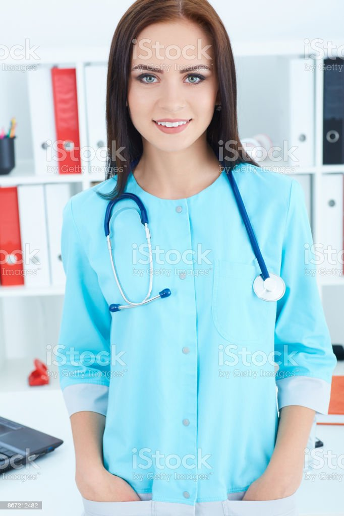Portrait of young smiling woman doctor with blue coat standing in hospital. Medical help or insurance concept. stock photo