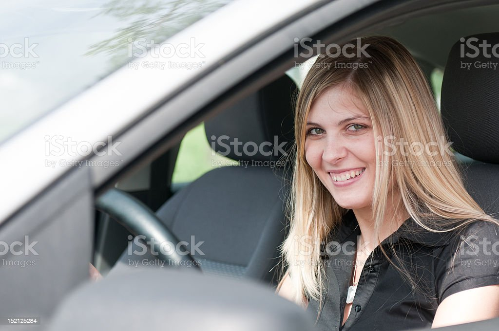 Portrait of young smiling woman driving car royalty-free stock photo