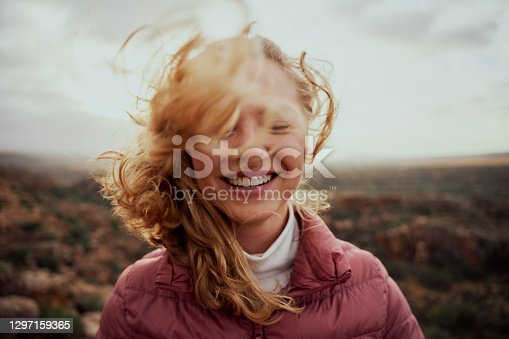 istock Portrait of young smiling woman face partially covered with flying hair in windy day standing at mountain - carefree woman 1297159365