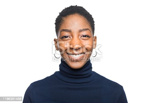 Shot of happy young woman with short hair against white background. Close-up portrait of african female looking at camera and smiling.