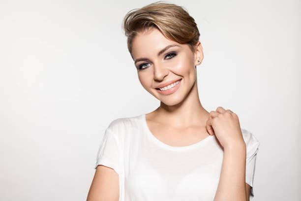 Portrait of young smiling woman with modern shot hairstyle stock photo
