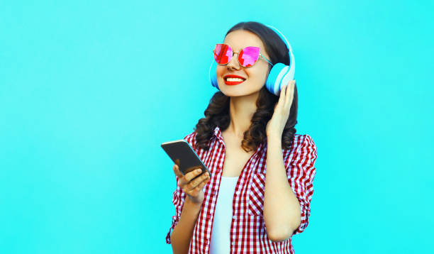 Portrait of young smiling woman with smartphone in wireless headphones listening to music wearing a pink sunglasses on colorful blue background stock photo
