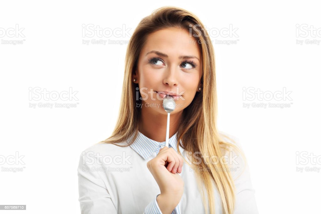 Portrait of young smiling woman with spoon in her mouth isolated on white