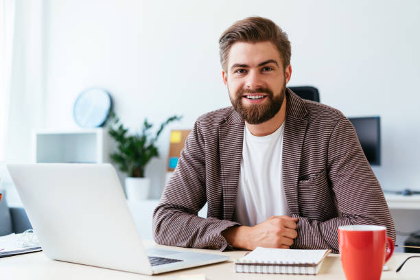 Portrait of young startup businessman sitting in small modern office and looking at camera stock photo