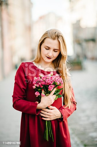 Portrait of young stylish beautiful girl in a red dress with bouquet of flowers stand on the street, smiling enjoy her weekends. Summer, sunny, trendy, lifestyle.