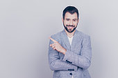 istock Portrait of young successful brunete  bearded stock-market broker guy on the pure light background, he is smiling, wearing suit and is pointing on a copyspace with his finger 936398452