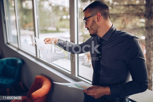 921587490 istock photo Portrait of young successful businessman sitting at his desk in the office. 1145329420